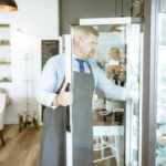 camarero de un restaurante abriendo cámara frigorífica.